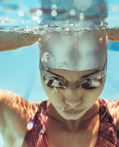 Kvinna med simglasögon och badmössa under vatten.